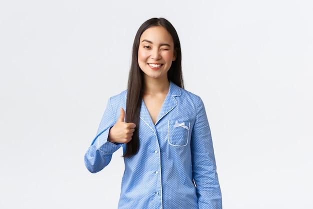 Allegra ragazza asiatica carina in pigiama blu che sorride compiaciuta e strizza l'occhio alla fidanzata, mostrando il pollice in su come lode grande festa per il pigiama party, mostrando supporto, dire ben fatto o buon lavoro, sfondo bianco