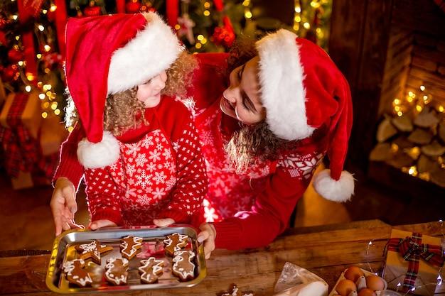 Bambina riccia sveglia allegra e sua sorella maggiore in cappelli di santa che cucinano i biscotti di natale