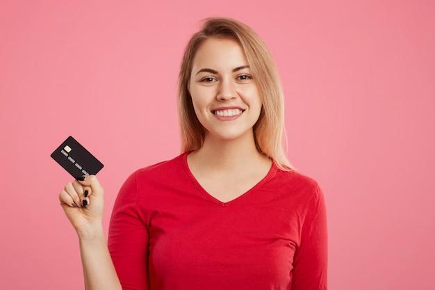 La donna bionda deliziosa allegra tiene la carta di plastica, felice di andare a fare spese e di ricevere la somma forfettaria di soldi sul suo conto, vestita in maglione rosso, isolato sul rosa. concetto di pagamento