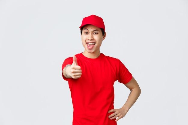 Il ragazzo delle consegne allegro in uniforme incoraggia a fare più ordini facendo acquisti online. bel corriere asiatico pollice in su, garantisce la migliore qualità o la spedizione dei pacchi, trasferisce i pacchi ai clienti.