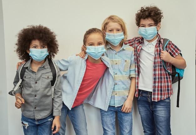 Bambini allegri e diversi che indossano maschere protettive che guardano la telecamera posare insieme sopra