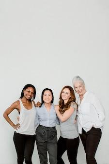 Donne allegre e diverse vicino alla finestra in una stanza bianca