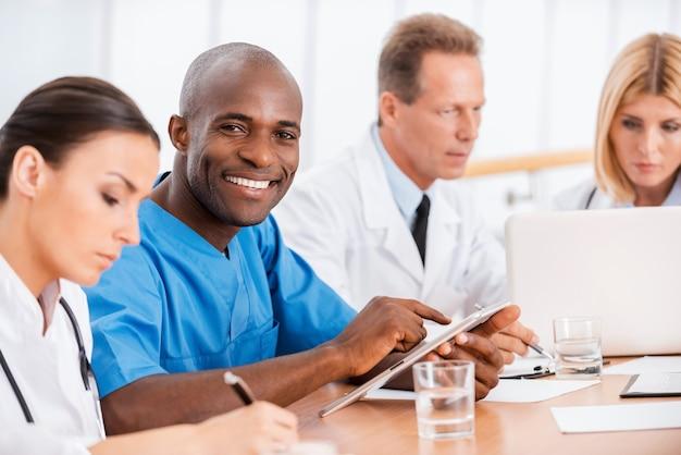 Medico allegro alla riunione. bel giovane medico africano che sorride mentre è seduto insieme ai suoi colleghi alla riunione