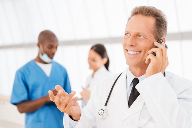 Medico allegro al telefono. medico maturo allegro che parla al telefono cellulare e che fa gesti mentre i suoi colleghi parlano in sottofondo