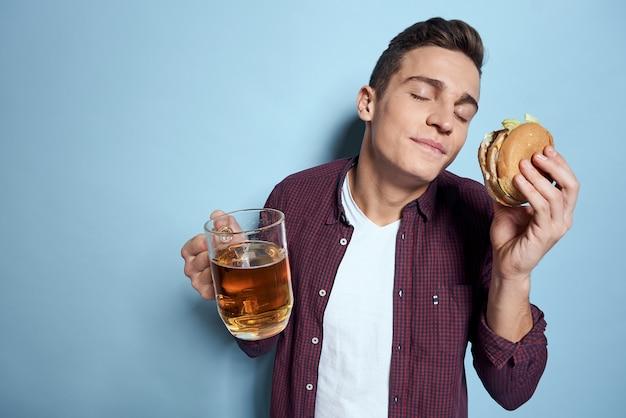 Allegro uomo ubriaco con boccale di birra e hamburger in mano dieta alimentare lifestyle parete blu.