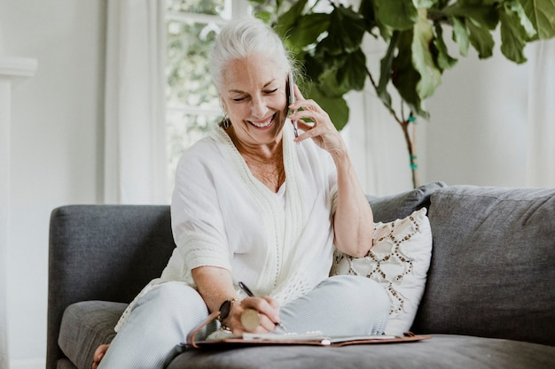 Donna anziana allegra che parla su un telefono su un divano
