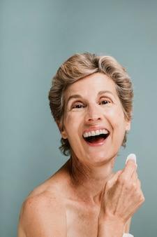 Donna anziana allegra che si asciuga il viso con un batuffolo di cotone