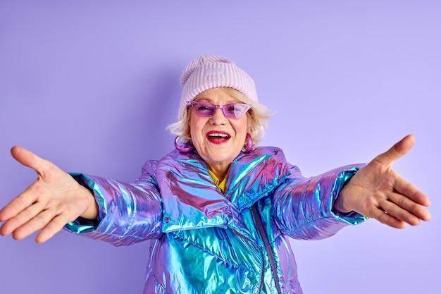 Allegra donna anziana con le braccia aperte guarda la fotocamera