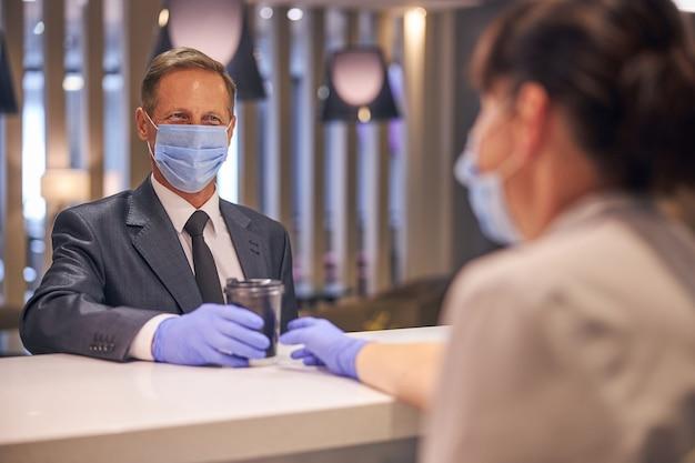 Il maschio elegante e allegro viene servito da una cameriera nel bar dell'aeroporto durante la quarantena