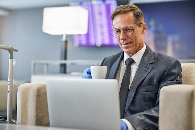 Un maschio elegante e allegro in guanti e occhiali in lattice sta bevendo caffè e sta usando il taccuino prima del volo