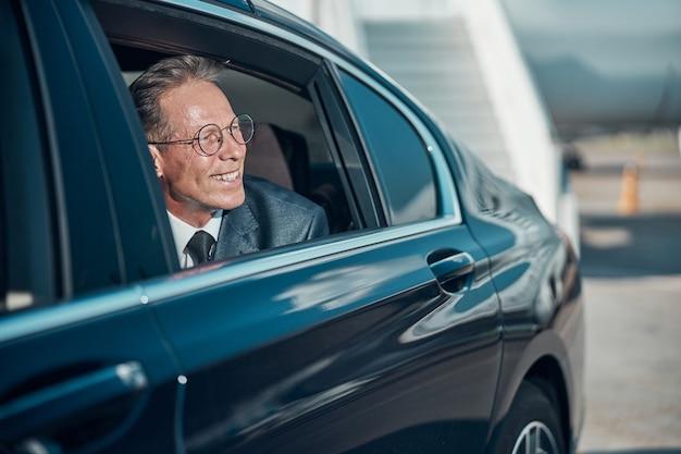 Un uomo elegante e allegro con gli occhiali si occupa del finestrino dell'automobile durante il trasferimento dopo l'atterraggio in aereo
