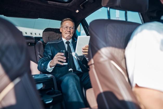 L'uomo allegro ed elegante è seduto nel retro dell'auto con il touchpad e una tazza di caffè dopo essere arrivato dal viaggio