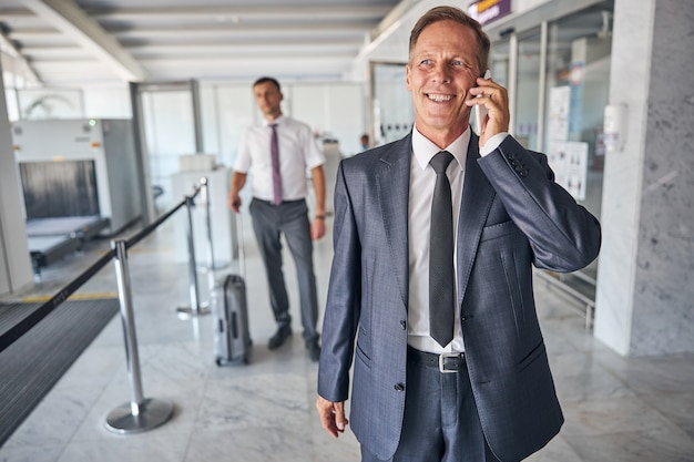 L'uomo elegante e allegro in cravatta sta camminando in aeroporto e parlando sullo smartphone mentre la guardia del corpo sta trasportando i bagagli