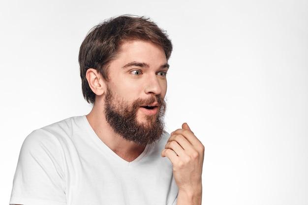 Uomo barbuto emotivo allegro che gesturing con la luce del primo piano delle mani.