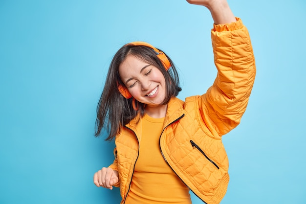 La ragazza asiatica allegra energica inclina la testa ha i capelli scuri che fluttuano nell'aria tiene il braccio alzato ascolta musica tramite cuffie wireless con piacere cattura ogni pezzo di canzone isolato sul muro blu