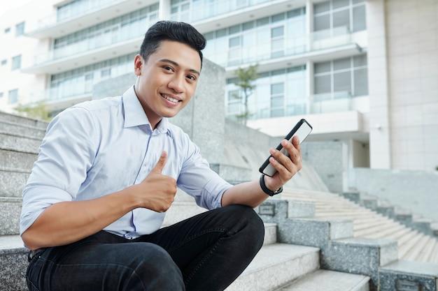 Allegro imprenditore con lo smartphone