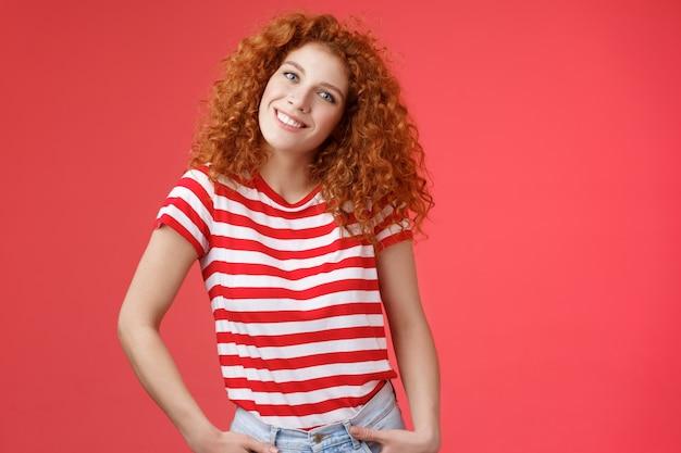 Allegra rossa europea alla moda rossa felice ragazza dai capelli ricci inclinare la testa eccitata tenersi per mano je...
