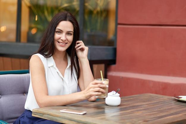 La donna europea allegra gode del tempo libero, beve il frappè alla caffetteria all'aperto, trascorre il weekend in una grande città, aspetta una chiamata sullo smart phone, sembra positiva, vestita in elegante camicetta bianca