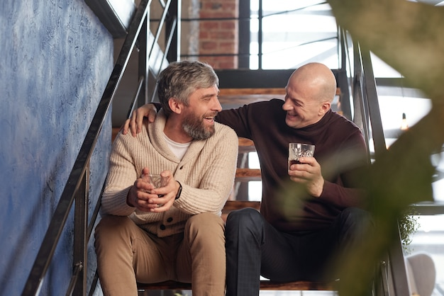 Uomini di mezza età entusiasti allegri che si siedono sulle scale e bevono whisky divertendosi a casa
