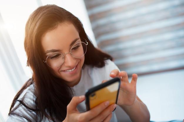 Il brunette positivo emozionante allegro utilizza uno smartphone giallo nella sua casa.