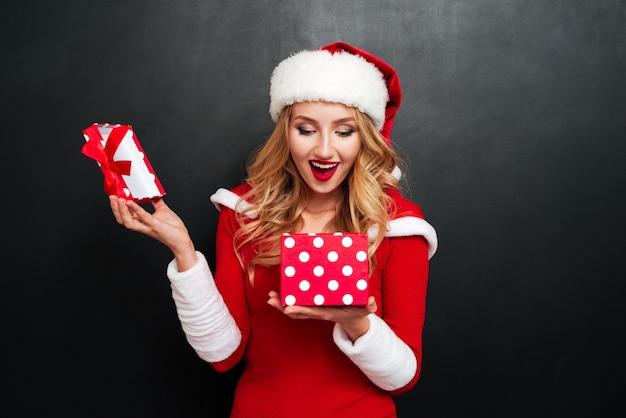 Giovane donna allegra eccitata in costume di babbo natale che apre la scatola del regalo