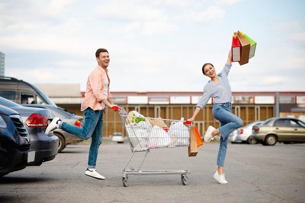 Coppia famiglia allegra con borse nel carrello sul parcheggio del supermercato. clienti felici che trasportano acquisti dal centro commerciale, veicoli sullo sfondo