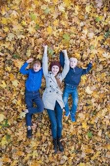 Famiglia allegra che scherza nel parco. madre e due bambini sdraiati in un grande mucchio di foglie. vista dall'alto. cornice verticale.