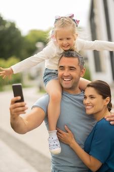 Sorridere allegro della famiglia. famiglia allegra che sorride mentre fa selfie tutti insieme in piedi fuori