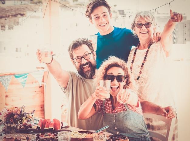 Famiglia allegra tre generazioni che si abbracciano mangiando cibo vegano insieme sul tavolo di legno