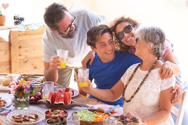 Famiglia allegra, tre generazioni, che si abbracciano mangiando insieme cibo vegano