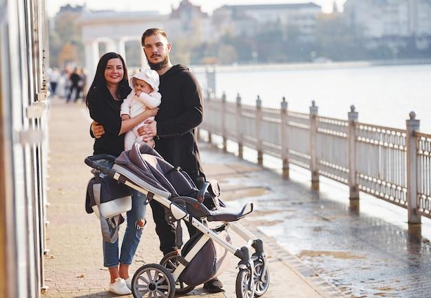 La famiglia allegra con la carrozzina fa una passeggiata insieme al loro bambino nel parco.
