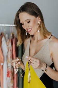 Fashionista allegra che seleziona gioielli in un negozio