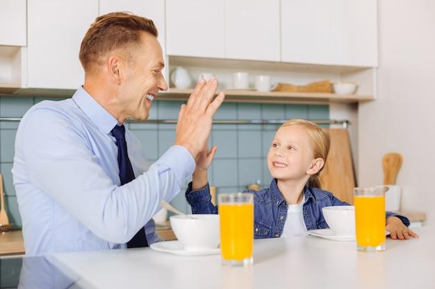 Padre e figlia allegri che si siedono uno di fronte all'altro e si danno il cinque