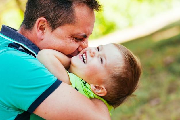 Padre allegro che si diverte con il suo piccolo figlio nel parco.