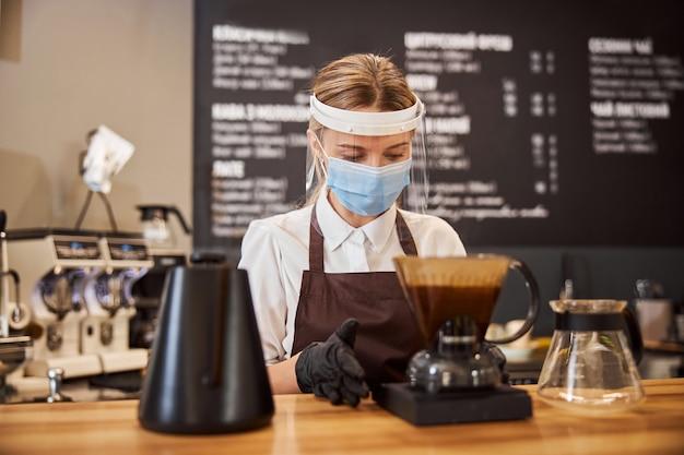 Barista femminile allegra che prepara caffè usando chemex versare sopra la caffettiera