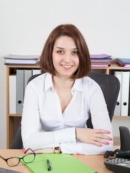 Impiegato femminile allegro della call center che indossa camicia e vetri bianchi