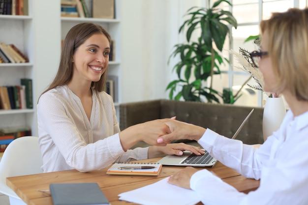 Psicologo medico femminile allegro che stringe le mani grate del paziente dopo aver avuto una riunione di consultazione.
