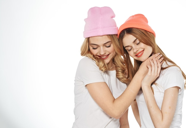 Allegre amiche in cappelli multicolori abbracciano lo stomaco gioia sfondo chiaro. foto di alta qualità