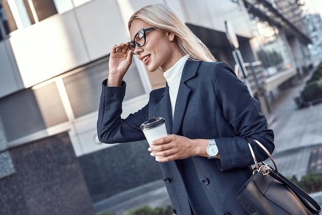 Manager femminile allegro che va al lavoro bevendo a piedi la mattina