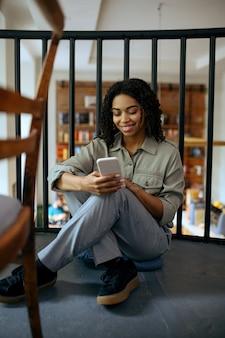 Allievo femminile allegro con il telefono che si siede sul pavimento nella caffetteria della biblioteca. donna che impara una materia, un'istruzione e una conoscenza. ragazza che studia nella caffetteria del campus