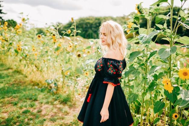 Femmina allegra in abiti tradizionali slavi in posa in girasoli all'aperto