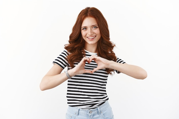 Allegra ragazza rossa femminile in t-shirt a righe mostra il cuore vicino al petto e sorridente adorabile, esprime simpatia ed emozioni positive, in piedi muro bianco Foto Premium
