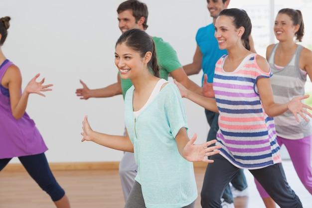 Classe ed istruttore allegri di forma fisica che fanno i pilates
