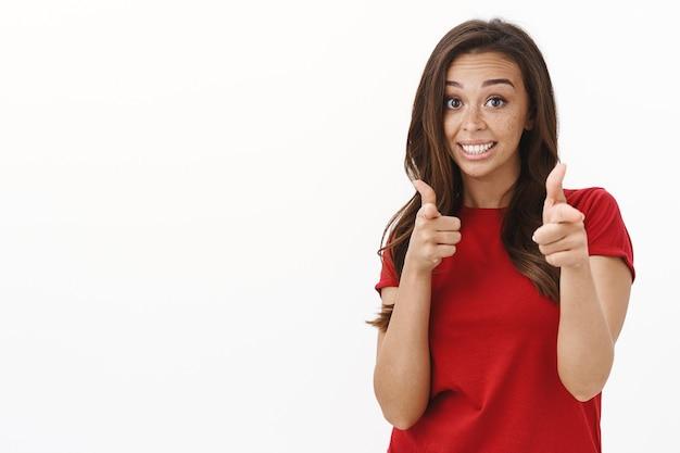 Allegra giovane ragazza bruna dall'aspetto amichevole con le lentiggini in maglietta rossa, che ti invita a unirti al suo viaggio, sorridendo stupido e modesto, puntando le pistole con il dito sul davanti come congratularmi con la persona o scherzando