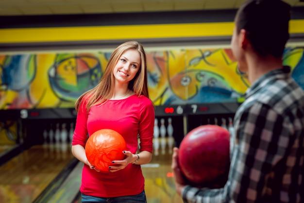 Amici allegri alla pista da bowling con le palle.