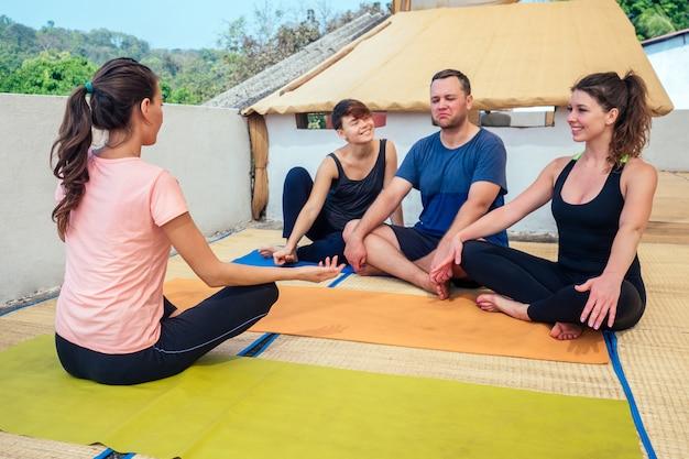 Amici allegri comunicano con un istruttore di yoga seduto sul pavimento in una lezione di yoga