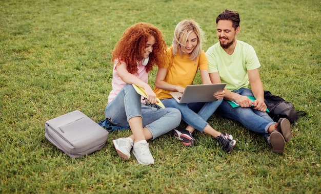 Amici allegri che fanno insieme il progetto dei compiti