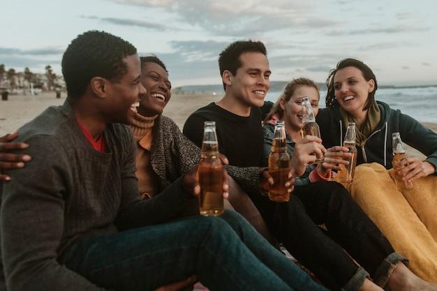 Amici allegri che bevono in riva al mare