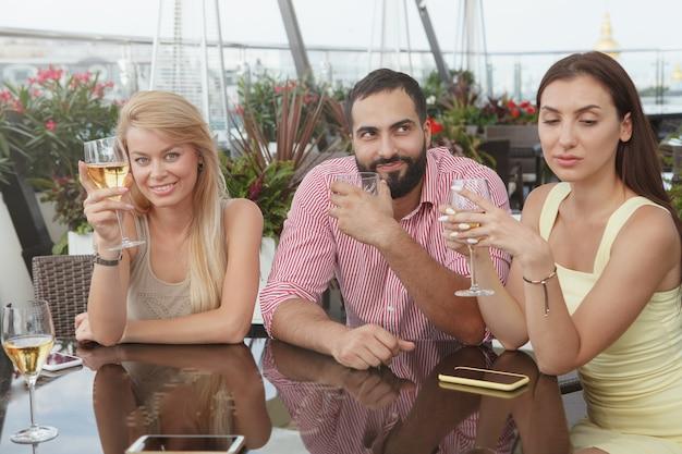 Amici allegri che godono di bere insieme al bar sul tetto