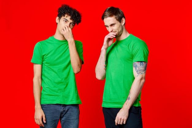 Amici allegri in magliette verdi che gesturing con le emozioni delle mani